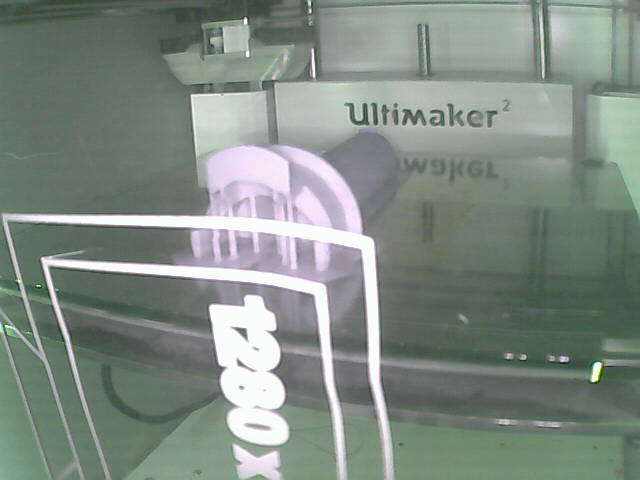 A view of the printbed of a 3D printer, showing a finished print of a spool holder